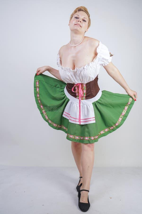 Muchacha linda del tamaño extra grande con un corte de pelo corto y pechos grandes vestidos en un vestido bávaro nacional en un f fotos de archivo libres de regalías
