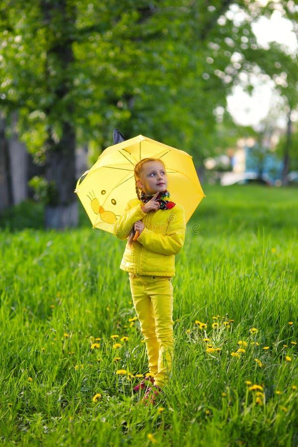 Muchacha linda divertida que lleva la capa amarilla que sostiene el paraguas colorido que juega en el jardín por el tiempo de la  imágenes de archivo libres de regalías