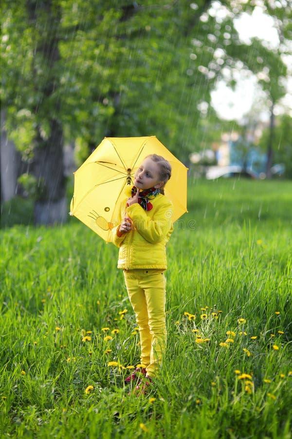 Muchacha linda divertida que lleva la capa amarilla que sostiene el paraguas colorido que juega en el jardín por el tiempo de la  imagen de archivo libre de regalías