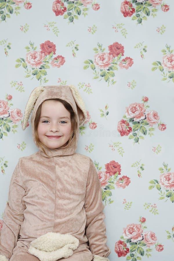 Muchacha linda en Bunny Costume Against Wallpaper imagenes de archivo