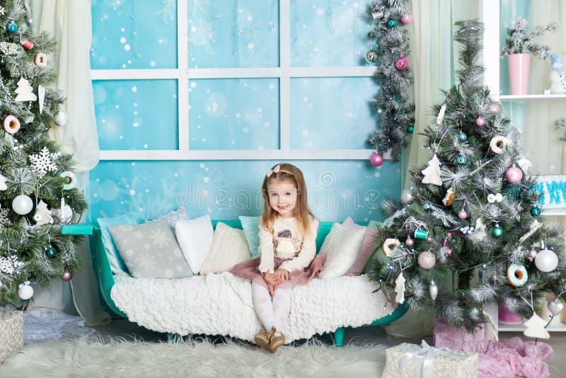 Muchacha linda en decoraciones de una Navidad fotografía de archivo