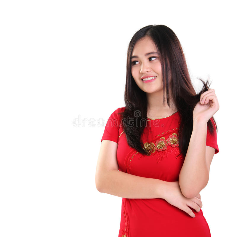 Muchacha linda en el cheongsam rojo que parece de lado aislado fotografía de archivo