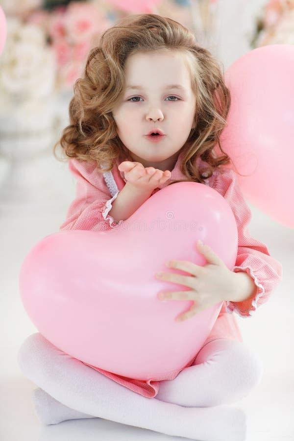 Muchacha linda en el piso blanco en estudio con un manojo de globos rosados fotos de archivo