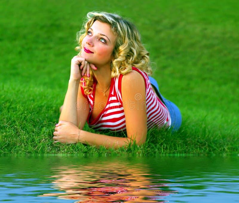 Muchacha linda en la hierba verde cerca del rivershore foto de archivo