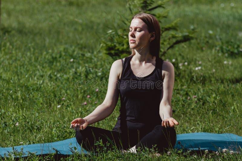 Muchacha linda en ropa negra en la hierba verde que hace yoga Goce de la meditaci?n y del sol brillante Se divierte forma de vida fotografía de archivo libre de regalías