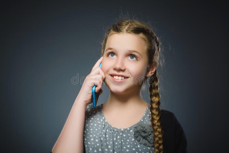 Muchacha linda feliz con el teléfono celular Aislado en gris fotos de archivo