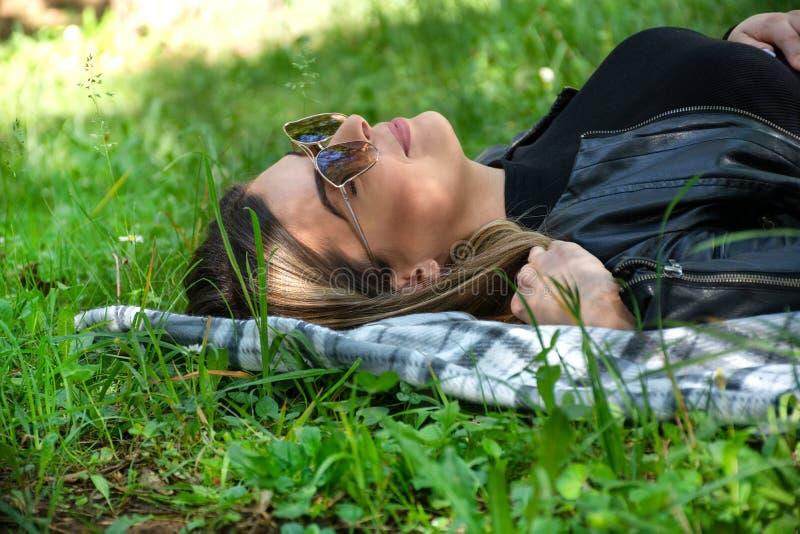 Muchacha linda feliz con las gafas de sol que mienten en una manta en hierba de prado el día soleado de la primavera foto de archivo libre de regalías