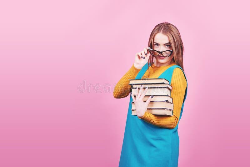 Muchacha linda feliz en los vidrios que sostienen en manos una pila de libros aislados en fondo rosado colorido imagenes de archivo