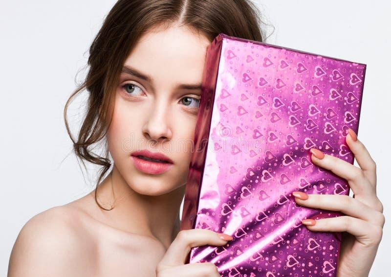 Muchacha linda feliz que lleva a cabo el presente de la caja de regalo de cumpleaños foto de archivo libre de regalías