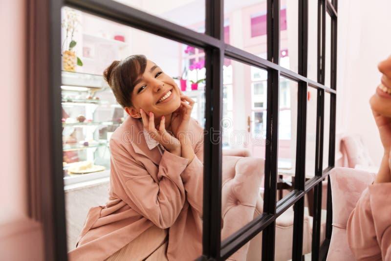 Muchacha linda feliz que mira el espejo y que sonríe dentro foto de archivo