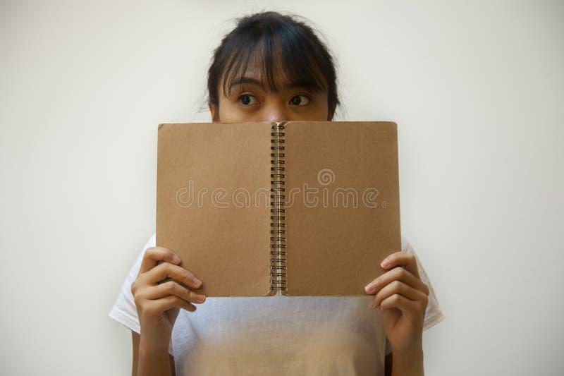Muchacha linda filipina asiática del adolescente que oculta su cara detrás del fondo marrón del cuaderno imagen de archivo libre de regalías