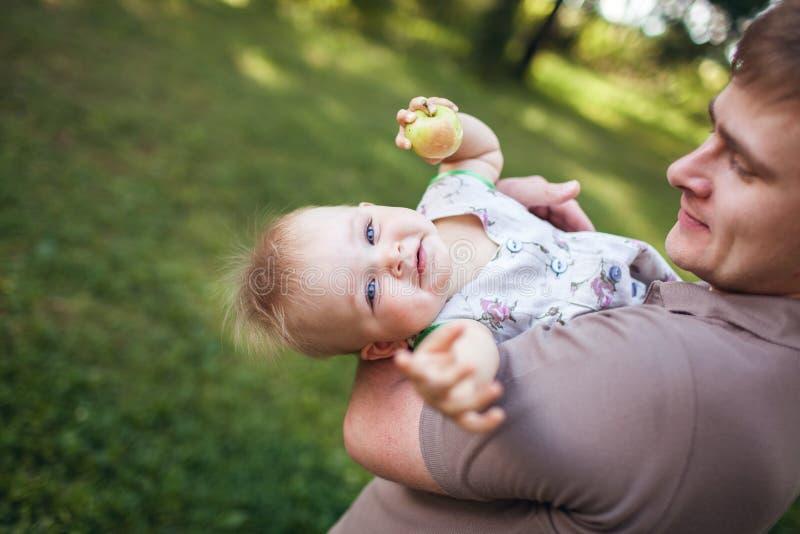 Muchacha linda hermosa en los brazos del papá imagenes de archivo