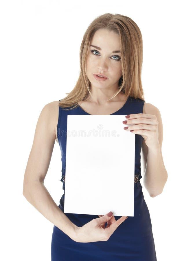 Muchacha linda hermosa en una alineada azul marino que sostiene una hoja en blanco o imagen de archivo libre de regalías