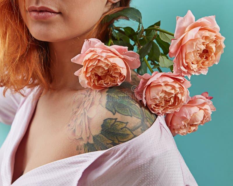 Muchacha linda joven con el tatuaje en sus hombros y un ramo de rosas coralinas en un fondo azul Postal para mimar a d?a del ` s fotos de archivo libres de regalías