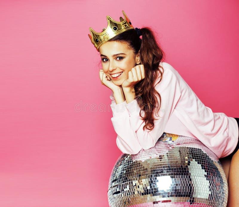 Muchacha linda joven del disco en fondo rosado con la bola y la corona foto de archivo libre de regalías