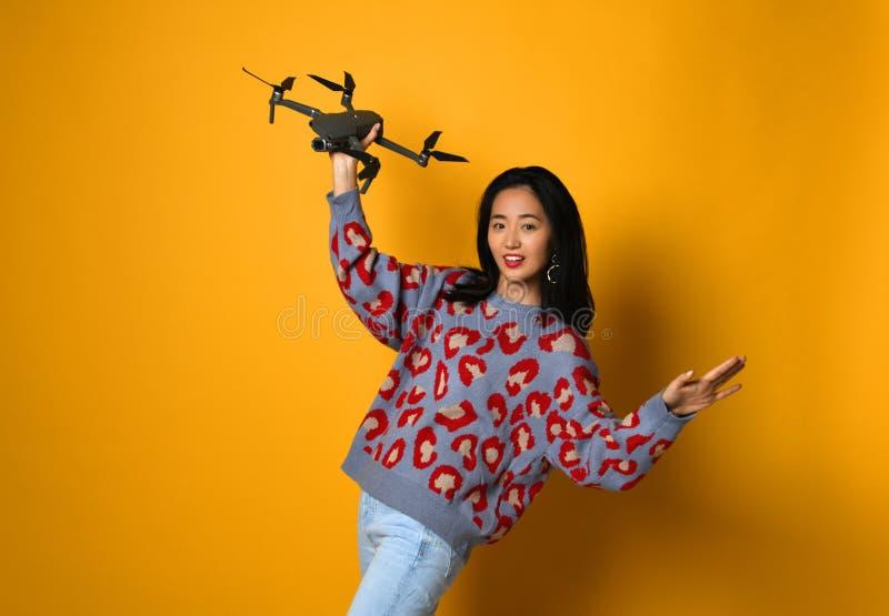 Muchacha linda joven que lleva a cabo el quadcopter Niño que juega con el abejón Educación, niños, tecnología, ciencia, futuro y  fotografía de archivo