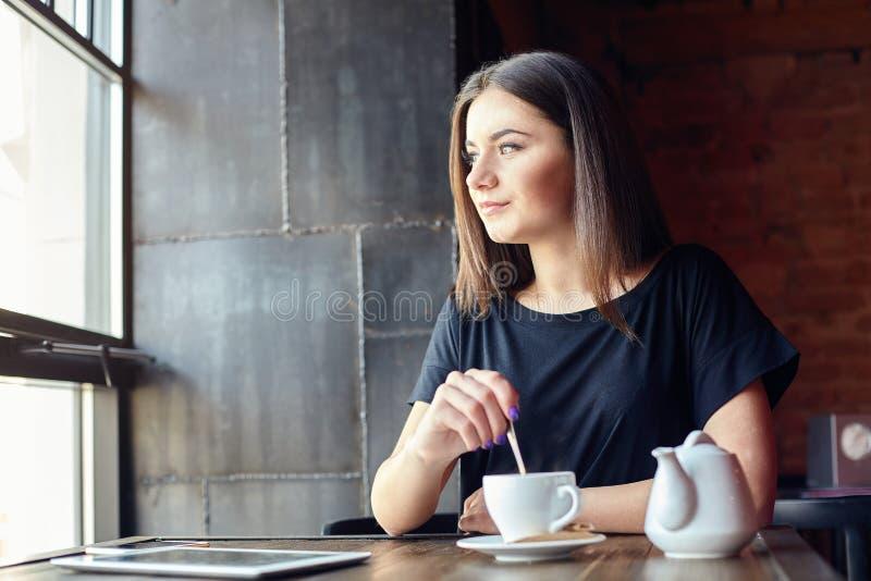 Muchacha linda joven que se sienta en café cerca de ventana y del sueño foto de archivo libre de regalías