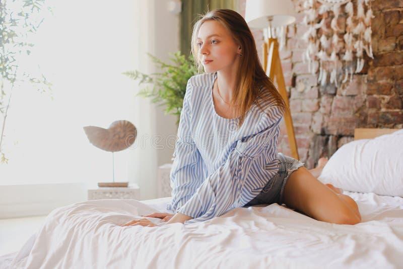 Muchacha linda joven que se sienta en cama Belleza, comodidad y relajación imagen de archivo libre de regalías