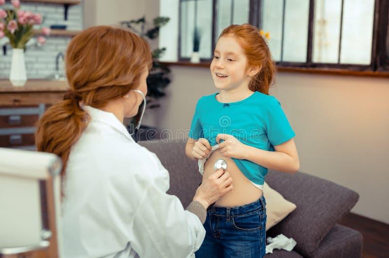 Muchacha linda positiva que muestra su vientre al doctor foto de archivo libre de regalías