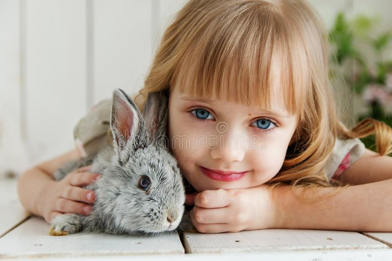 Muchacha linda que abraza con el conejo mientras que miente en el piso en casa imagen de archivo