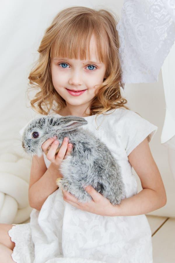 Muchacha linda que abraza con el conejo mientras que se sienta en el piso en casa fotos de archivo