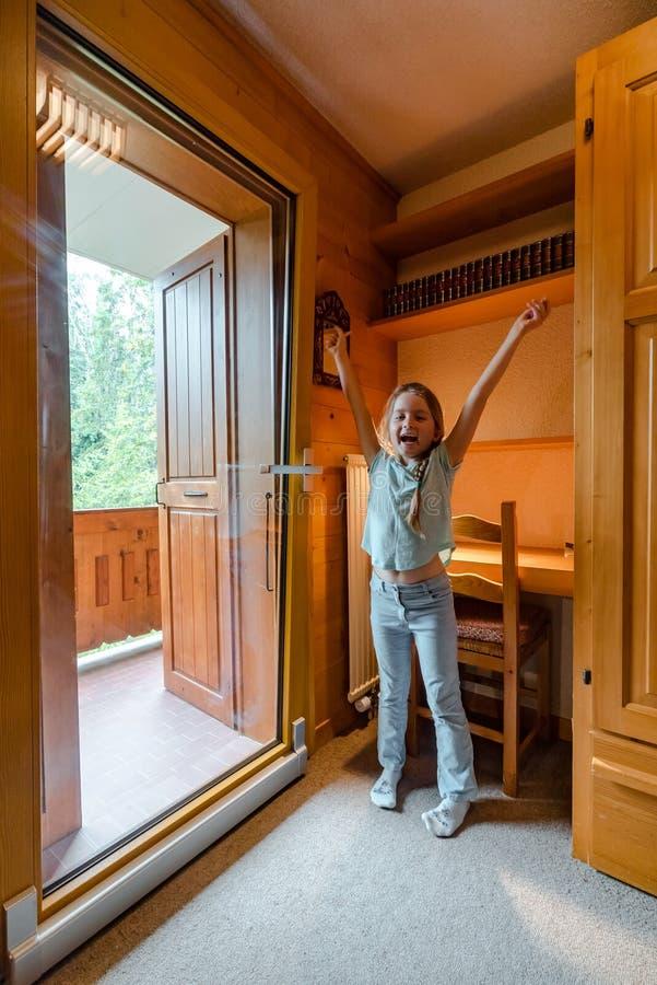 Muchacha linda que abre la puerta deslizante de cristal grande en el balcón foto de archivo libre de regalías