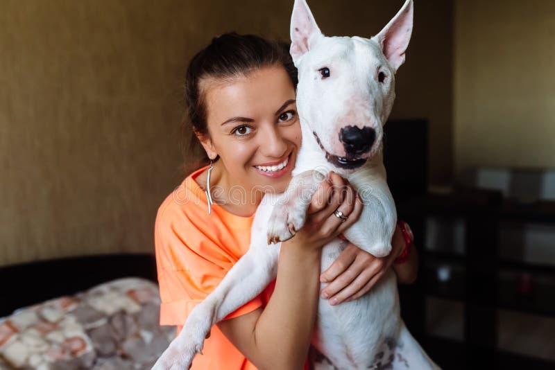 Muchacha linda que acaricia su bull terrier Muchacha hermosa que se divierte con su bull terrier y que se goza Muchacha y ella fotografía de archivo libre de regalías