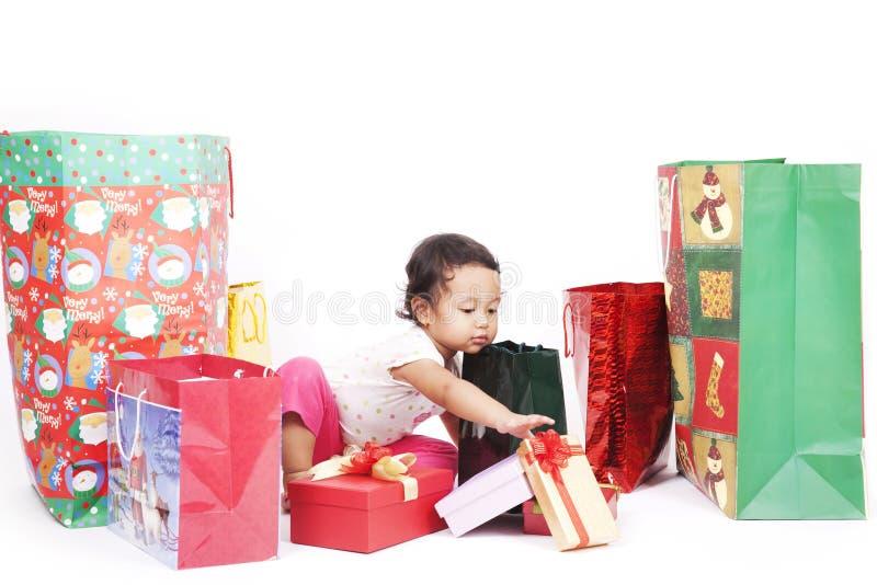 Muchacha linda que busca para el regalo de Navidad fotografía de archivo libre de regalías