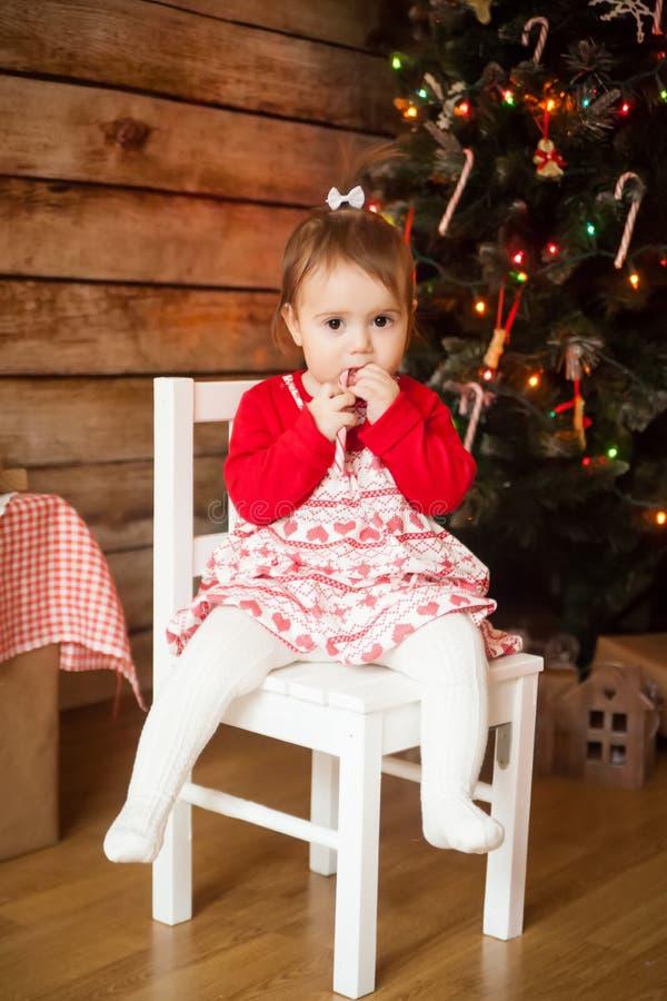 Muchacha linda que come el bastón de caramelo torcido de la Navidad fotografía de archivo