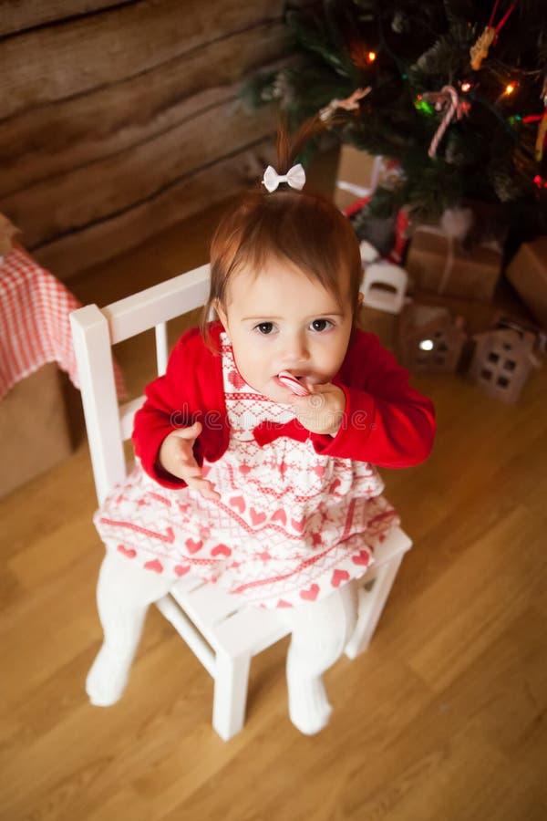 Muchacha linda que come el bastón de caramelo torcido de la Navidad imagenes de archivo