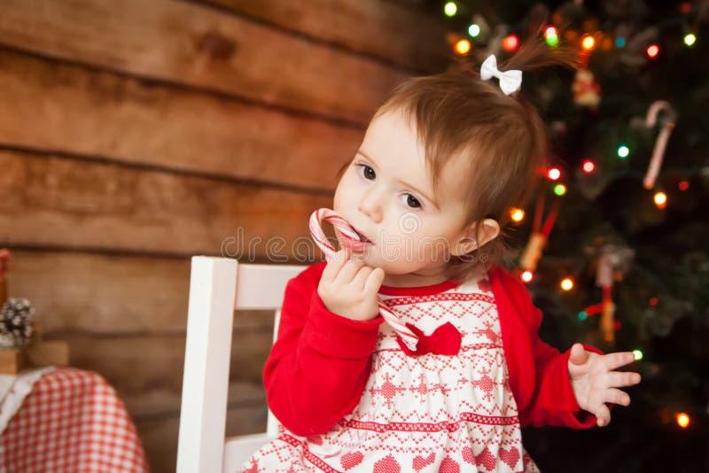 Muchacha linda que come el bastón de caramelo torcido de la Navidad imágenes de archivo libres de regalías