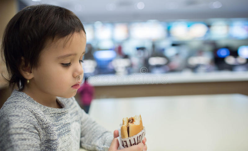 Muchacha linda que come una hamburguesa en los alimentos de preparación rápida fotografía de archivo libre de regalías