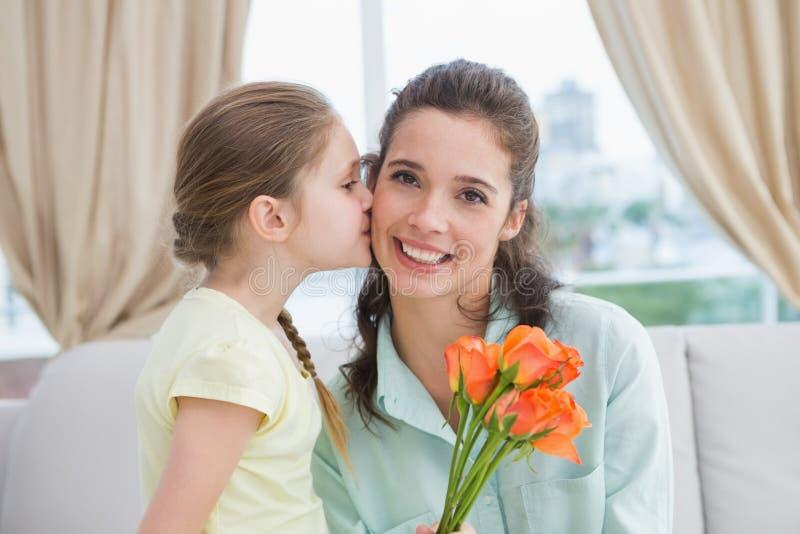 Muchacha linda que da las flores a la madre imagen de archivo libre de regalías