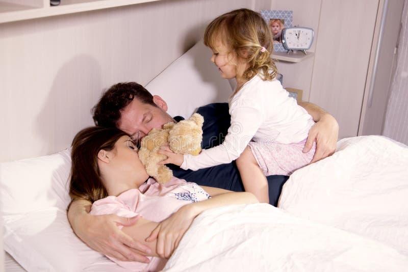 Muchacha linda que despierta la madre y al padre en dormir de la cama fotografía de archivo libre de regalías