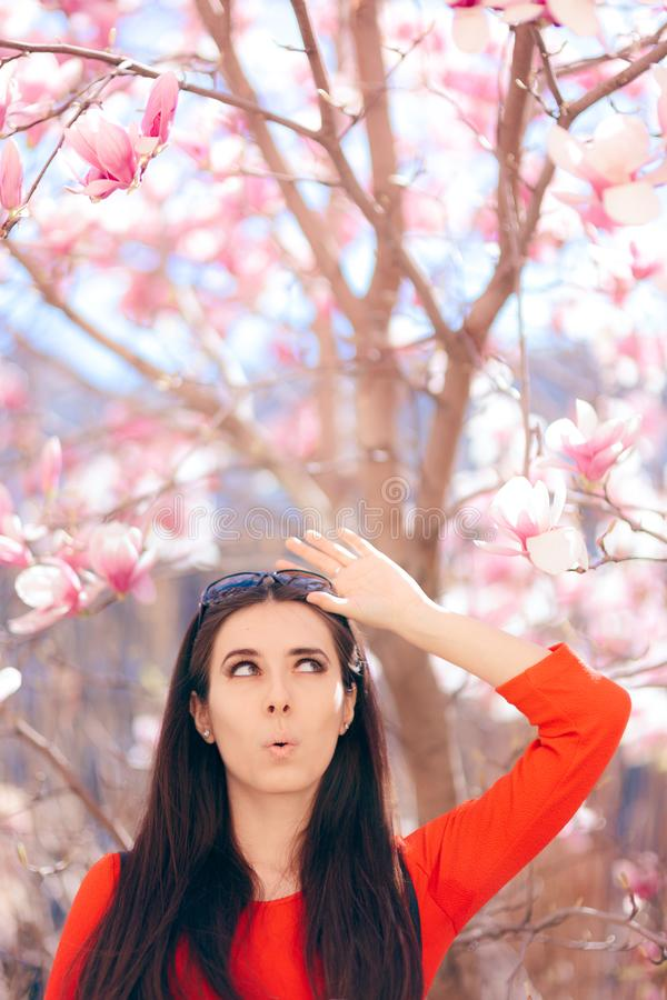 Muchacha linda que disfruta de la primavera Sun al lado del árbol de la magnolia imagenes de archivo