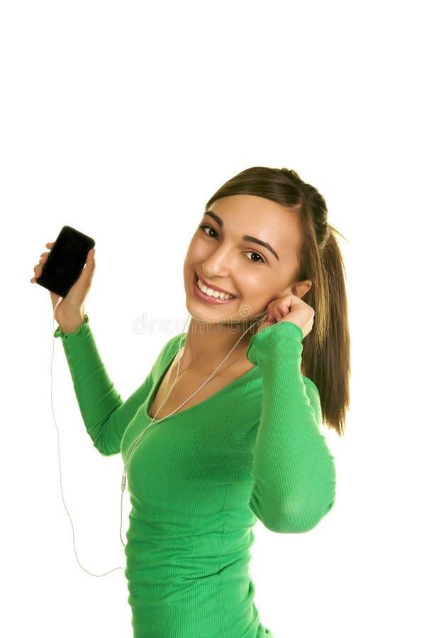 Muchacha linda que escucha sus consonancias imagen de archivo