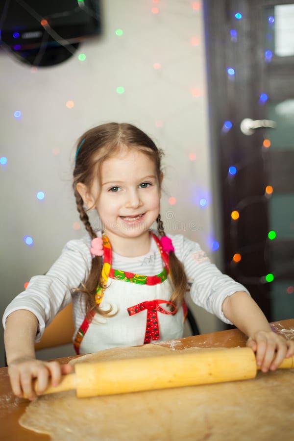 Muchacha linda que hace la pasta para las galletas fotos de archivo