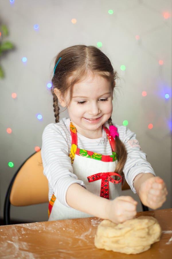 Muchacha linda que hace la pasta para las galletas imagen de archivo