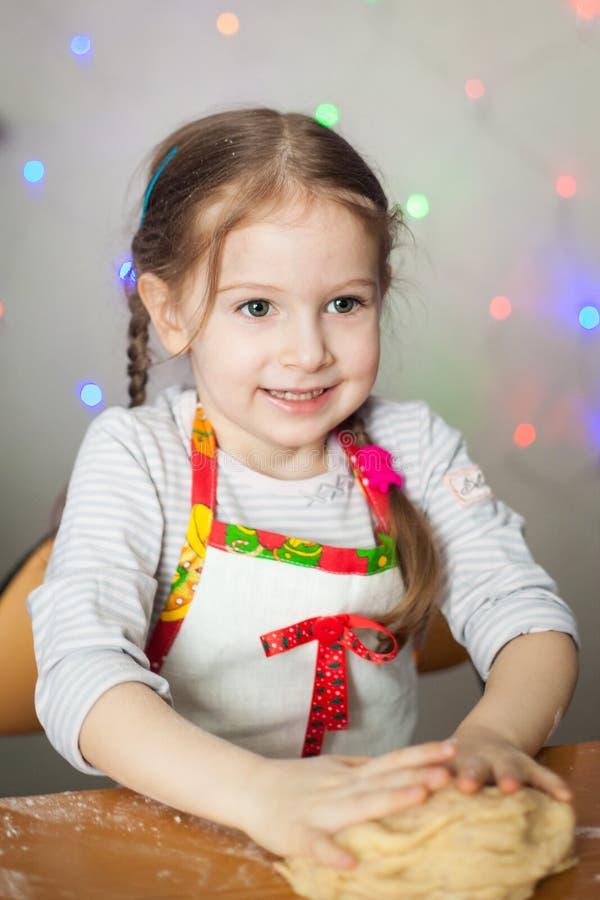Muchacha linda que hace la pasta para las galletas fotografía de archivo