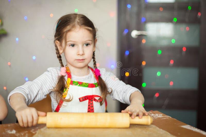Muchacha linda que hace la pasta para las galletas imagenes de archivo