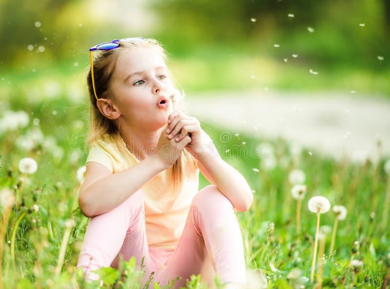 Muchacha linda que juega con los dientes de le?n fotos de archivo libres de regalías