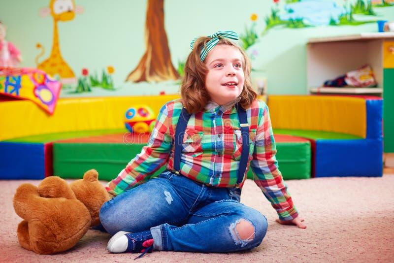Muchacha linda que juega en la guardería para los niños con necesidades especiales fotos de archivo