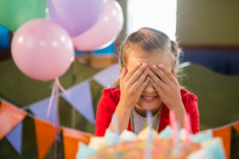 Muchacha linda que la cubre ojos durante fiesta de cumpleaños imágenes de archivo libres de regalías