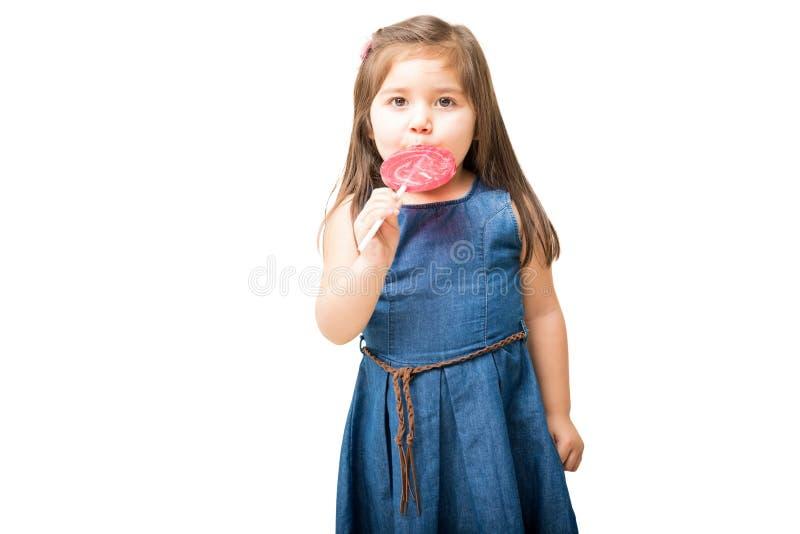 Muchacha linda que lame el caramelo colorido de la piruleta fotos de archivo