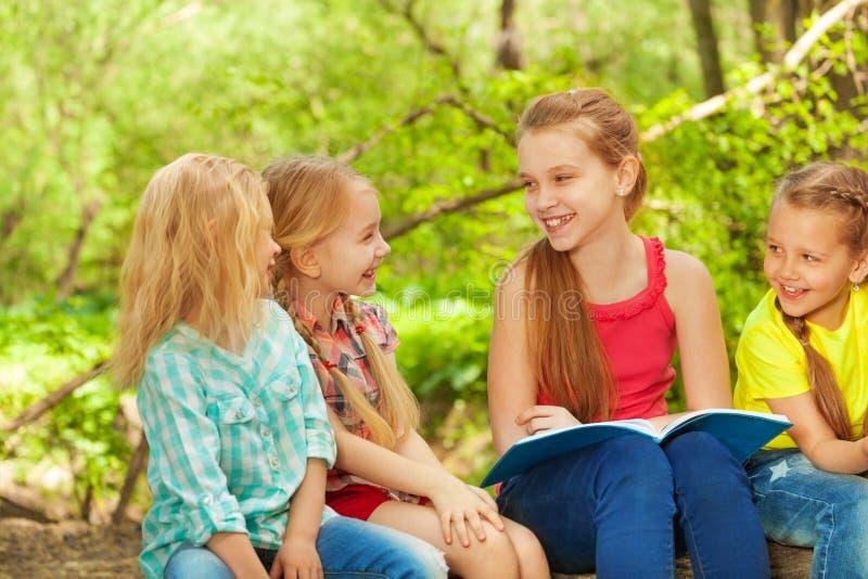 Muchacha linda que lee el libro a sus amigos al aire libre fotos de archivo