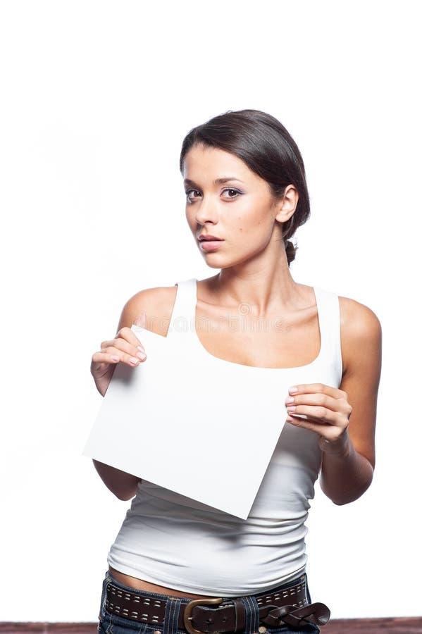 Muchacha linda que lleva a cabo la muestra blanca en el fondo blanco foto de archivo