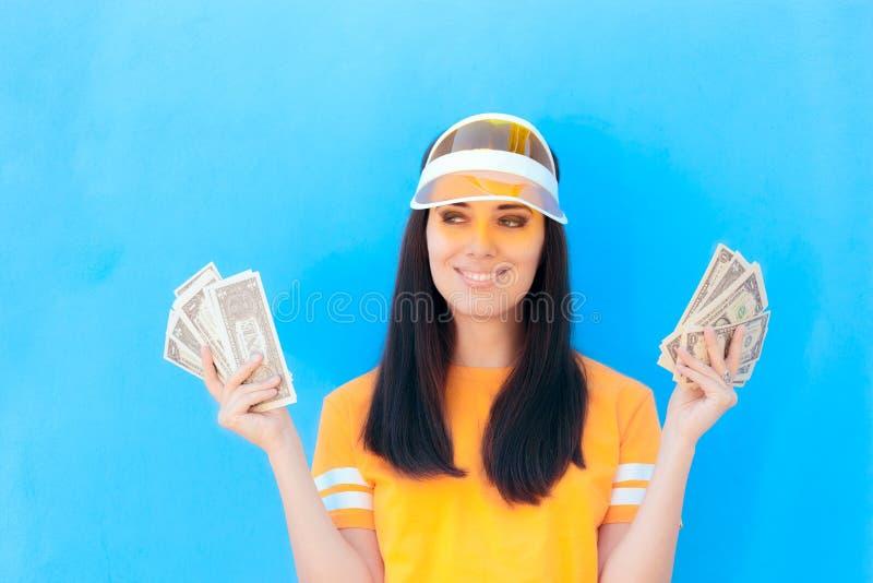 Muchacha linda que lleva a cabo sus ahorros del dinero en billetes de banco del dólar fotografía de archivo libre de regalías