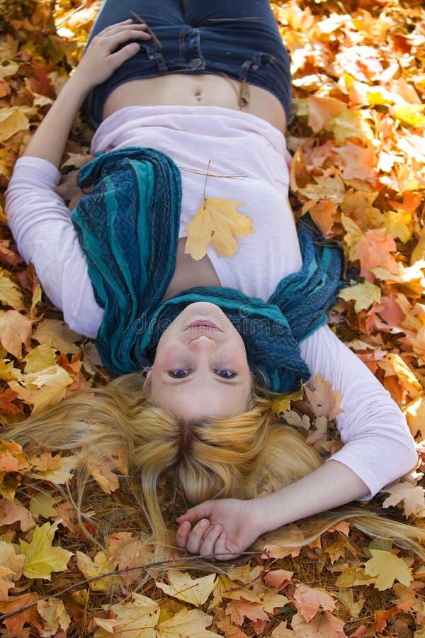 Muchacha linda que miente en las hojas de la caída fotografía de archivo