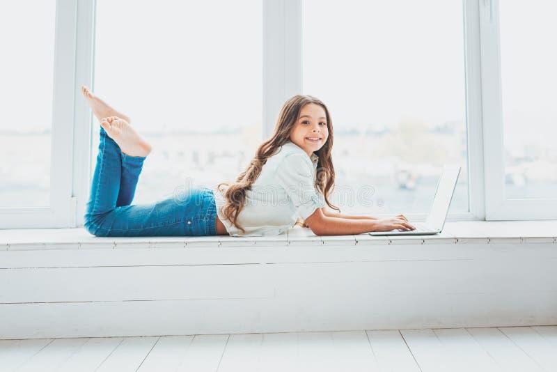 Muchacha linda que miente en travesaño de la ventana delante del ordenador portátil imagen de archivo