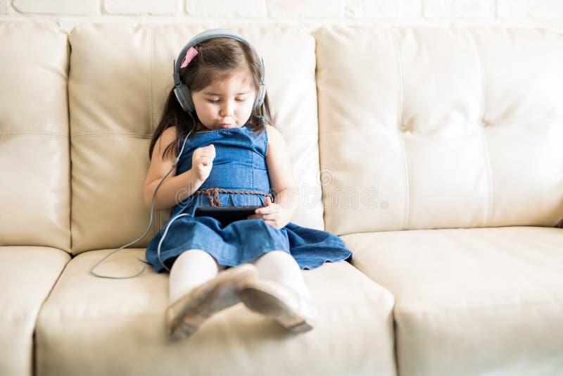 Muchacha linda que mira su película favorita en el teléfono celular foto de archivo libre de regalías